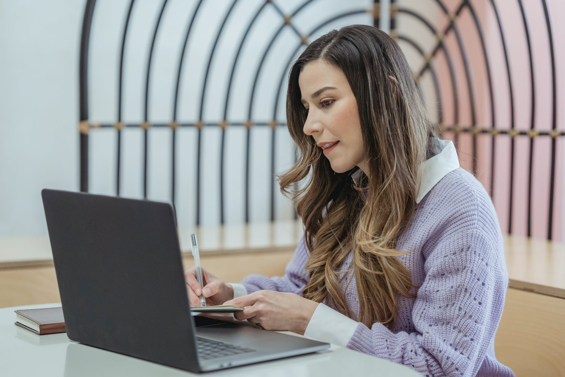 positive woman writing in notebook and watching laptop