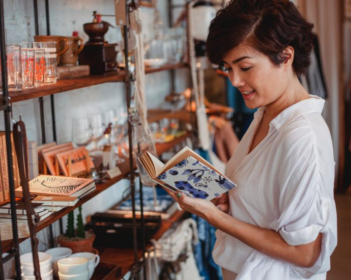 gorgeous asian young lady reading novel in vintage boutique